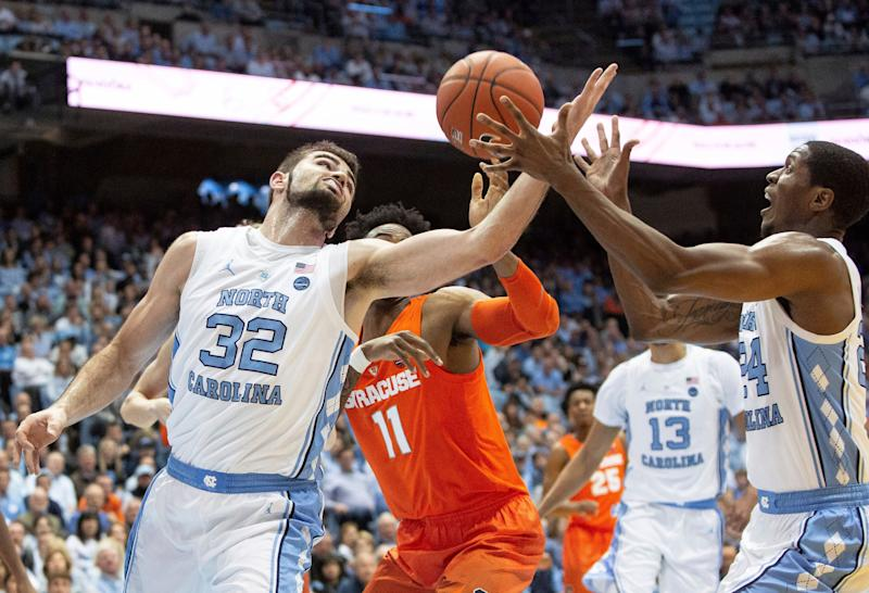 North Carolina's Luke Maye (32) and Kenny Williams (24), and Syracuse's Oshae Brissett (11) battle for a rebound during the first half of an NCAA college basketball game in Chapel Hill, N.C., Tuesday, Feb. 26, 2019. (AP Photo/Ben McKeown)