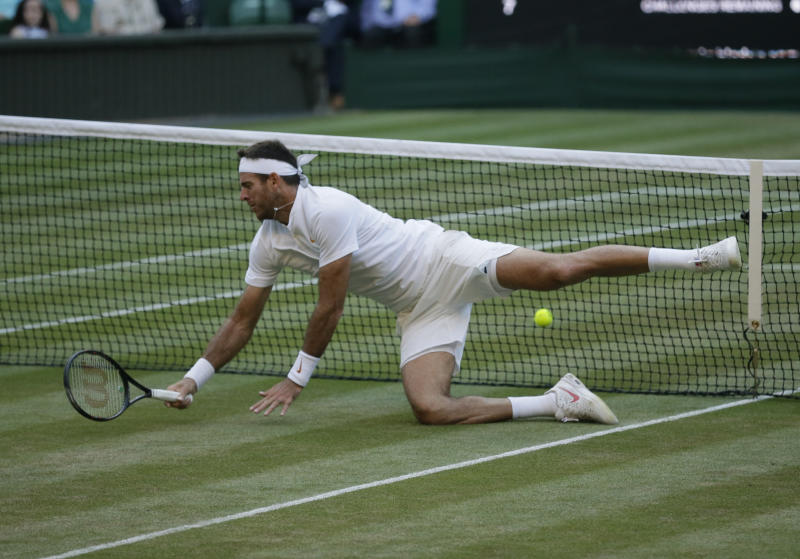 Juan Martin Del Potro of Argentina falls on the court during the men's quarterfinal match against Rafael Nadal of Spain at the Wimbledon Tennis Championships in London Wednesday