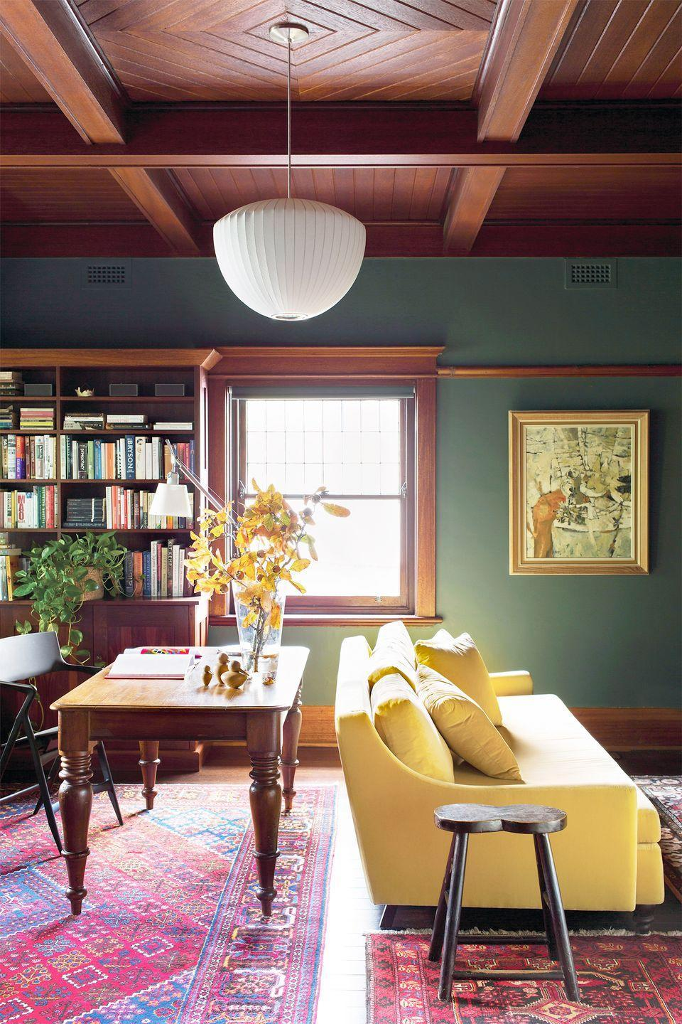 <p>A moody shade of army green paint complements the mahogany wood details in this living room, while the sunny yellow sofa and pink layered rugs brighten up the space. </p>