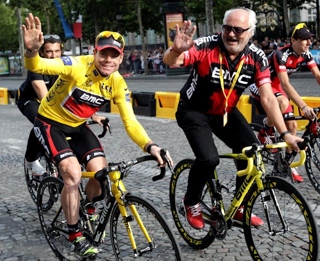 FILE PHOTO: BMC Racing Team's Cadel Evans of Australia (L), wearing the leader's yellow jersey, celebrates on the Champs Elysees next to Andy Rihs, co-owner of the BMC team, after he won the 98th Tour de France cycling race in Paris July 24, 2011. REUTERS/Denis Balibouse/File Photo