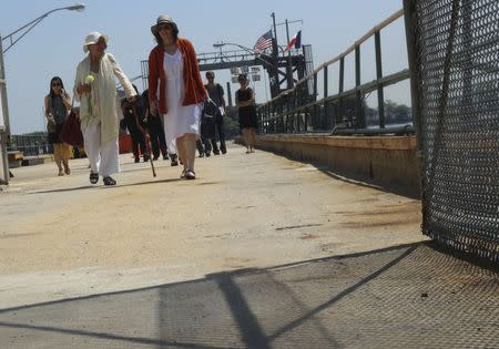 Rosalee Grable, (L) walks off the ferry to Hart's Island with Melinda Hunt in New York July 19, 2015.  REUTERS/Sebastien Malo