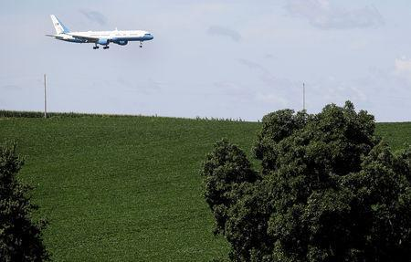 FILE PHOTO: Air Force One with U.S. President Donald Trump on board descends over a soybean field prior to landing at Dubuque Regional Airport in Dubuque, Iowa, U.S., July 26, 2018. REUTERS/Joshua Lott/File Photo