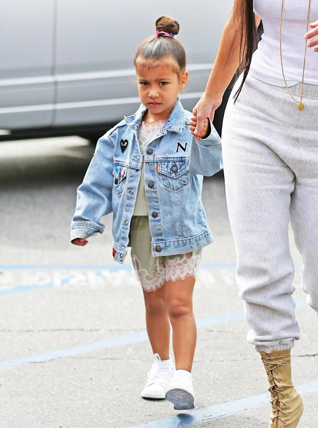 <p>Here with her personalized over-sized denim jacket, over a mint green lace slip dress. North West knows what's what. (Photo: Backgrid) </p>