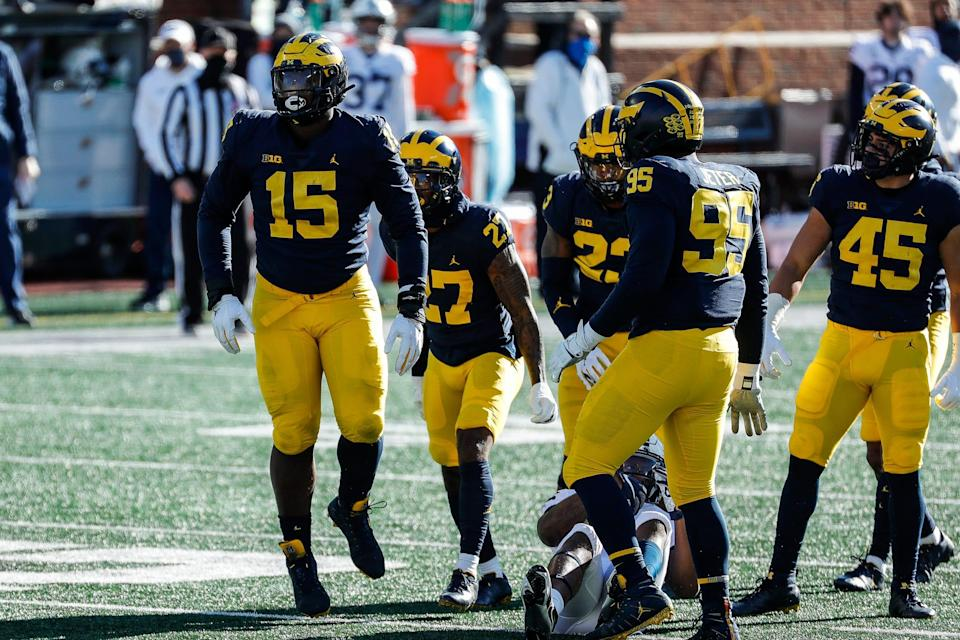 Michigan defensive lineman Christopher Hinton, left, celebrates a tackle against Penn State during the first half at Michigan Stadium in Ann Arbor, Saturday, Nov. 28, 2020.
