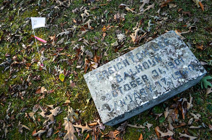 """A white flag """"SOL 21"""" is next to the gravestone of Creighton Lee Calhoun (1901-1940) in the gated plot Calhoun Plantation Cemetery, at Woodland Cemetery in Clemson."""