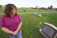 Sharon Grover looks down at the gravestone for her daughter, Rachael, Tuesday, Sept. 28, 2021, at Fairview Cemetery in Mesopotamia, Ohio. Grover believes her daughter started using prescription painkillers around 2013 but missed any signs of her addiction as her daughter, the oldest of five children, remained distanced. (AP Photo/Tony Dejak)
