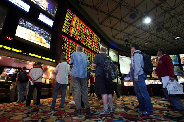FILE PHOTO: People wait in line to place bets after Super Bowl XLVIII proposition bets were posted at the Las Vegas Hotel & Casino Superbook in Las Vegas, Nevada, U.S., January 23, 2014. REUTERS/Las Vegas Sun/Steve Marcus/File Photo