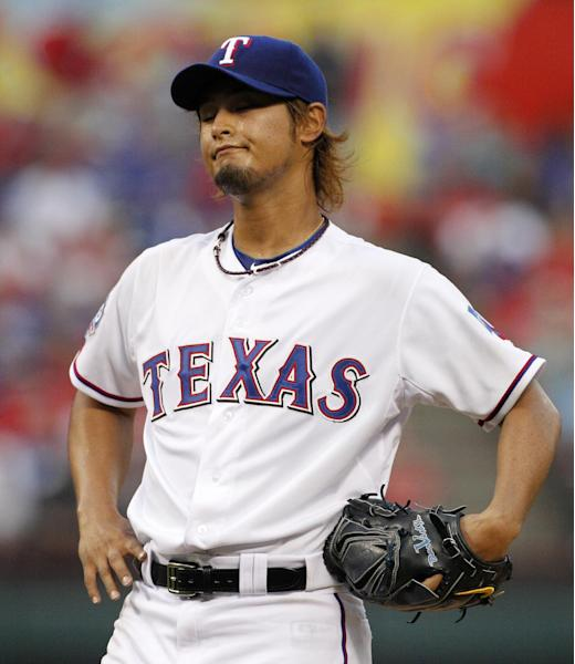 Texas Rangers' Yu Darvish of Japan grimaces after walking Seattle Mariners' Munenori Kawasaki of Japan in the first inning of a baseball game Monday, April 9, 2012, in Arlington, Texas. (AP Photo/Tony Gutierrez)