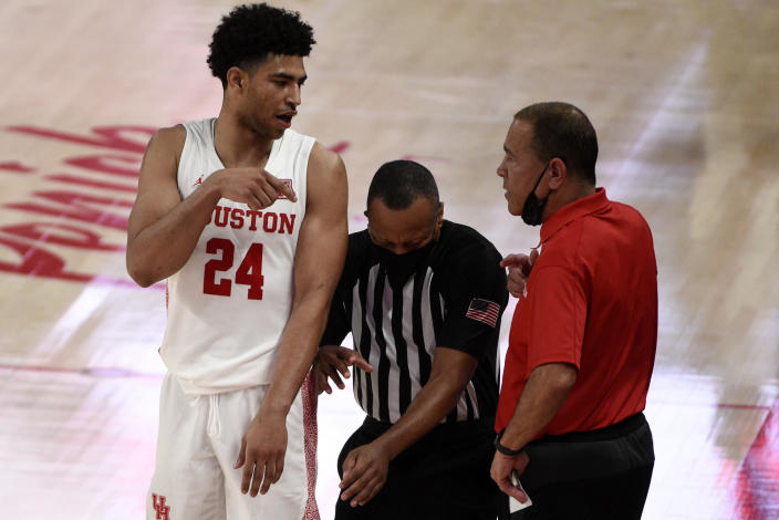 Houston head coach Kelvin Sampson, right, talks with guard Quentin Grimes (24) as an official, center, gets caught in the middle during the second half of an NCAA college basketball game against Cincinnati, Sunday, Feb. 21, 2021, in Houston. (AP Photo/Eric Christian Smith)