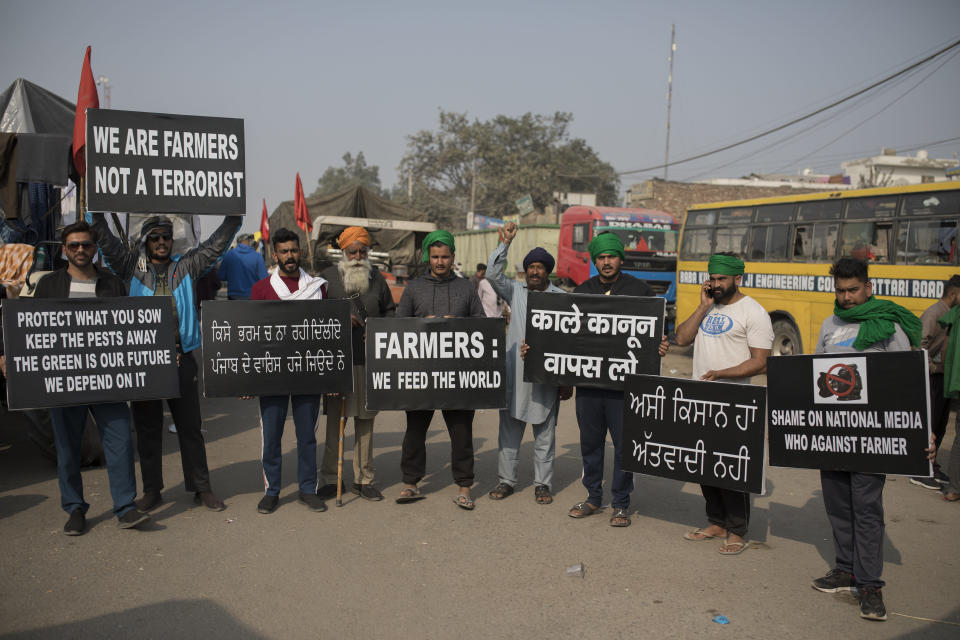 Protesting farmers hold placards at the border between Delhi and Haryana state, Tuesday, Dec. 1, 2020. Talks between protesting farmers and the Indian government failed Tuesday after both the parties could not reach a common ground to discuss the new farming laws, protests against which have intensified after entering their sixth day. More growers joined giant demonstrations and choked roads to India's Capital by hunkering down along with their trucks and tractors. (AP Photo/Altaf Qadri)