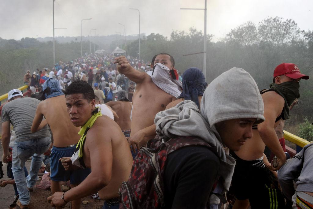 <p>Protesters throw stones against the Venezuelan security forces as locals try to clear a path for humanitarian aid to enter Venezuela at Francisco de Paula Santander bridge near the border between Colombia and Venezuela on Feb. 23, 2019 in Cucuta, Colombia. Opposition leader Juan Guaidó and self declared Venezuela's interim president began moving the supplies, including food and medicine, into Venezuela as President Maduro, in a speech delivered in Caracas, severed diplomatic ties with Colombia. (Photo from Manuel Hernndez/Vizzor Image/Getty Images) </p>