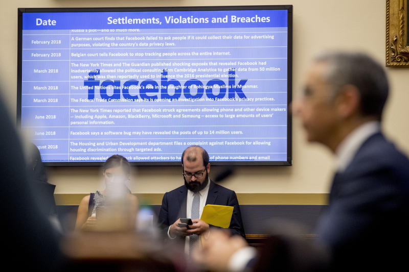 A list of settlements, violations and breaches scrolls over Facebook's logo on a screen as David Marcus, CEO of Facebook's Calibra digital wallet service, foreground, appears before a House Financial Services Committee hearing on Facebook's proposed cryptocurrency on Capitol Hill in Washington, Wednesday, July 17, 2019. (AP Photo/Andrew Harnik)