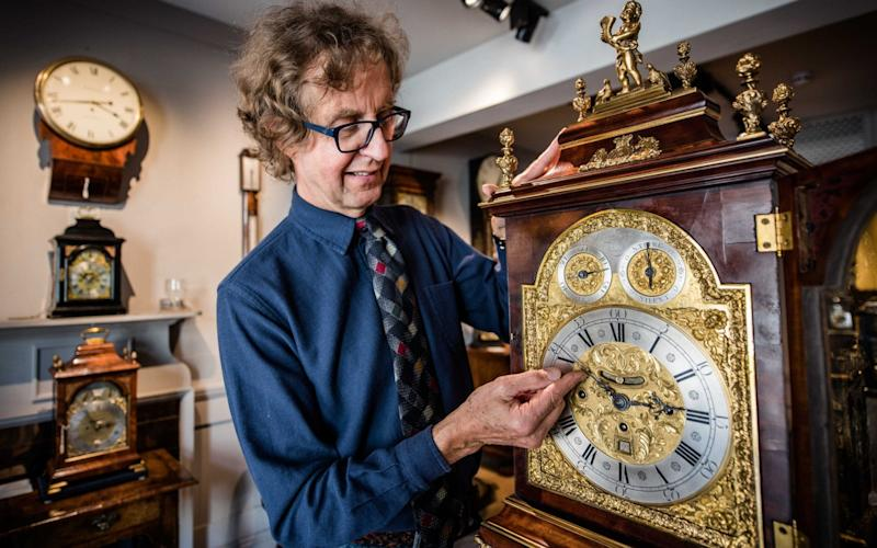 Antique clock seller Howard Walwyn goes through his shop in Kensington, London, changing the time on all the clocks - John Nguyen/JNVisuals