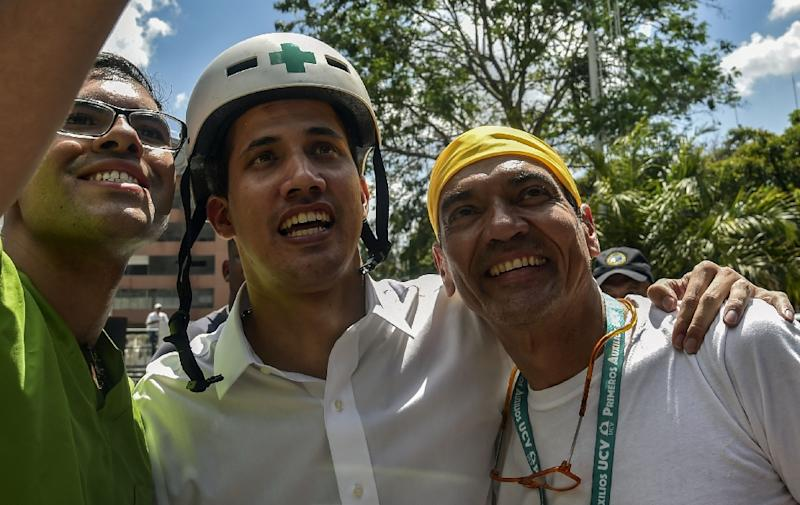 Venezuelan opposition leader and self-declared acting president Juan Guaido wears a Green Cross helmet as he posses for a picture with volunteers ready to help bring aid into the stricken country (AFP Photo/YURI CORTEZ)