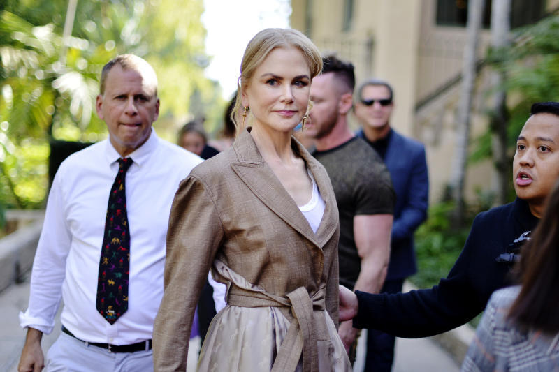 Nicole Kidman smiles at the camera wearing a brown trench coat