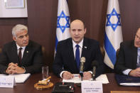 """Israeli Prime Minister Naftali Bennett, center, flanked by Alternate Prime Minister and Foreign Minister Yair Lapid, left, chairs the first weekly cabinet meeting of the new government in Jerusalem, Sunday, June 20, 2021. Bennett opened his first Cabinet meeting on Sunday since swearing in his new coalition government with a condemnation of the newly elected Iranian president, whom he called """"the hangman of Tehran."""" (Emmanuel Dunand/Pool Photo via AP)"""