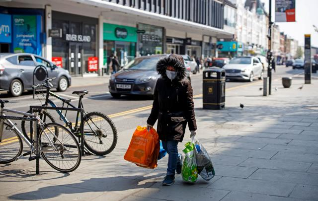 A woman wearing a protective face mask carries bags of shopping down a street in north London. (Tolga Akmen/AFP via Getty Images)
