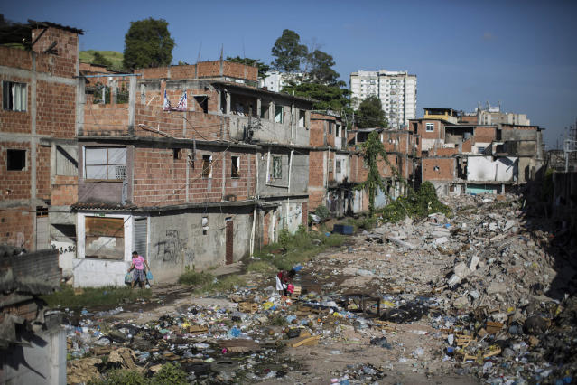 In this Jan. 9, 2014 photo, trash fills an area in the Favela do Metro slum outside Maracana stadium where some homes have been demolished and residents evicted in Rio de Janeiro, Brazil. Some residents in this slum were evicted from their homes two years ago for the area to be renovated for this year's World Cup and 2016 Olympics, but people reoccupied the homes and are fighting to stay. (AP Photo/Felipe Dana)