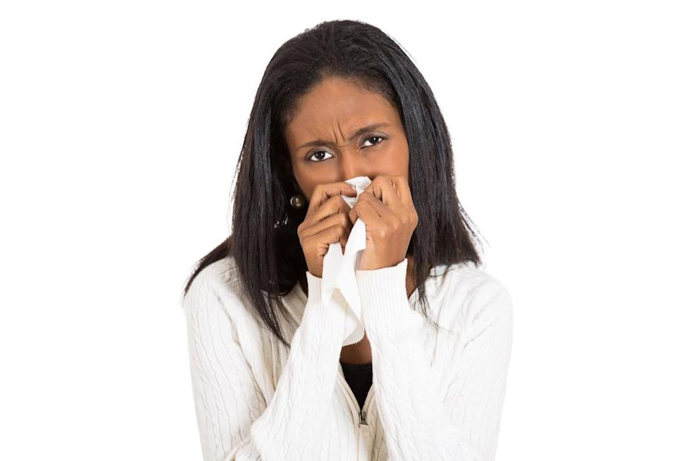 Closeup portrait sick young woman student, worker, employee with allergy, germs, cold, blowing nose with kleenex, looking miserable, unwell very sick, isolated on white background