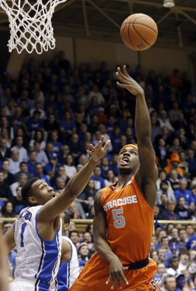 Duke's Jabari Parker (1) defends against Syracuse's C.J. Fair (5) during the first half of an NCAA college basketball game in Durham, N.C., Saturday, Feb. 22, 2014. (AP Photo/Gerry Broome)
