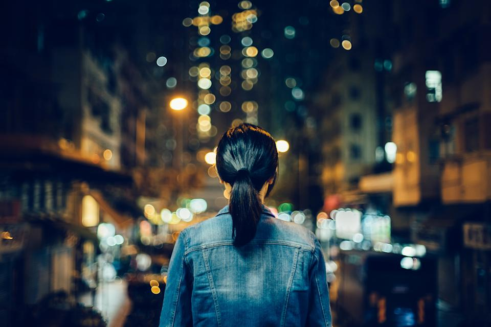 Rear view of young woman exploring city streets at night. (Photo: Getty Images)