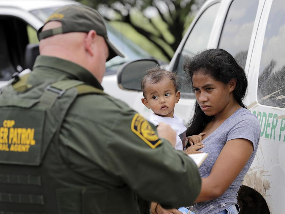 A mother migrating from Honduras holds her 1-year-old child as surrendering to U.S. Border Patrol agents after illegally crossing the border, near McAllen, Texas (AP)