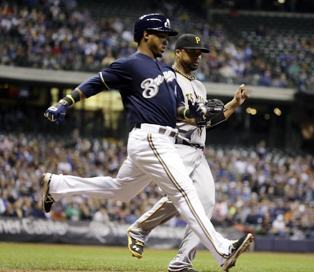 Milwaukee Brewers' Jean Segura beats Pittsburgh Pirates' Francisco Liriano to first during the fifth inning of a baseball game Wednesday, May 14, 2014, in Milwaukee. The play was ruled an error by first baseman Ike Davis. (AP Photo/Morry Gash)