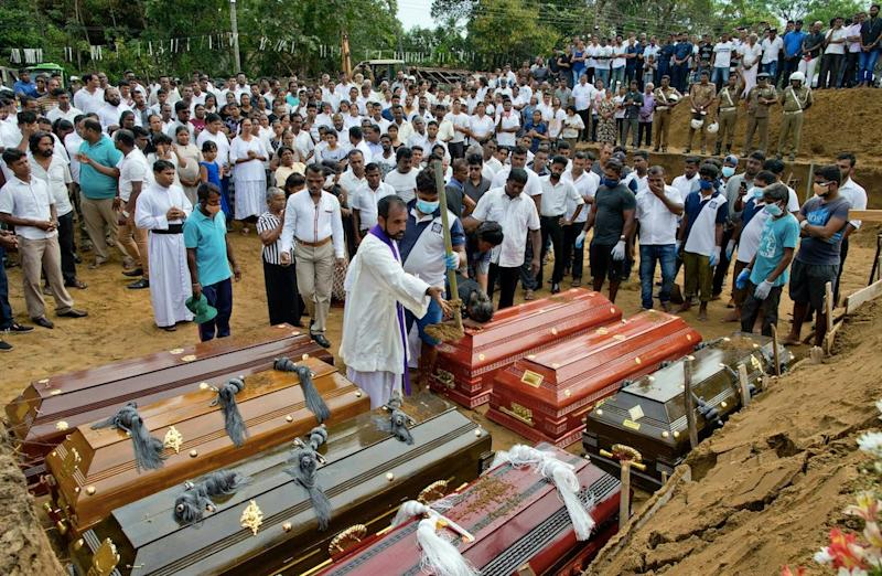 A priest conducts religious rituals during a mass burial for Easter Sunday bomb blast victims in Negombo, Sri Lanka (PA)