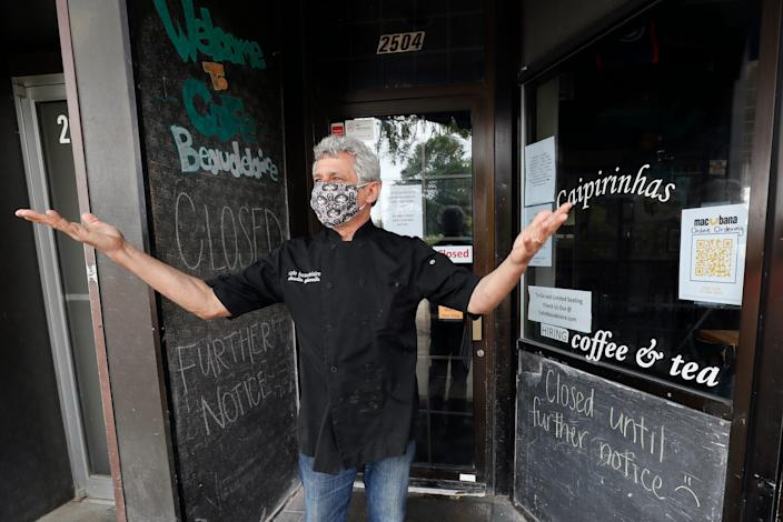 "Owner Claudio Gianello stands in the doorway of his temporarily closed Café Beaudelaire restaurant, on June 23, 2020, in Ames, Iowa, where the coronavirus surge is serious enough to prompt several business owners near the Iowa State University campus to close voluntarily just weeks after reopening. <p class=""copyright""><a href=""https://newsroom.ap.org/detail/VirusOutbreakCollegeTowns/865bbb449fc1427489f960e092d5d7e8/photo?Query=VIRUS%20OUTBREAK%20COLLEGE%20TOWNS&mediaType=photo,video&sortBy=arrivaldatetime:desc&dateRange=Anytime&totalCount=5&currentItemNo=4"" rel=""nofollow noopener"" target=""_blank"" data-ylk=""slk:AP Photo/Charlie Neibergall"" class=""link rapid-noclick-resp"">AP Photo/Charlie Neibergall</a></p>"