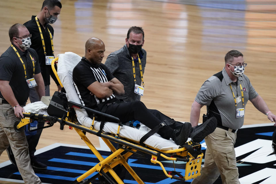 Referee Bert Smith is taken off the court on a stretcher after collapsing during the first half of an Elite 8 game between Gonzaga and Southern California during the first half of an Elite 8 game in the NCAA men's college basketball tournament at Lucas Oil Stadium, Tuesday, March 30, 2021, in Indianapolis. (AP Photo/Michael Conroy)