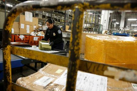 U.S. Customs and Border Protection officer Marlene Calderon opens packages, after they were X-rayed for contraband, at the JFK mail facility in New York, U.S., August 28, 2018. REUTERS/Jill Kitchener