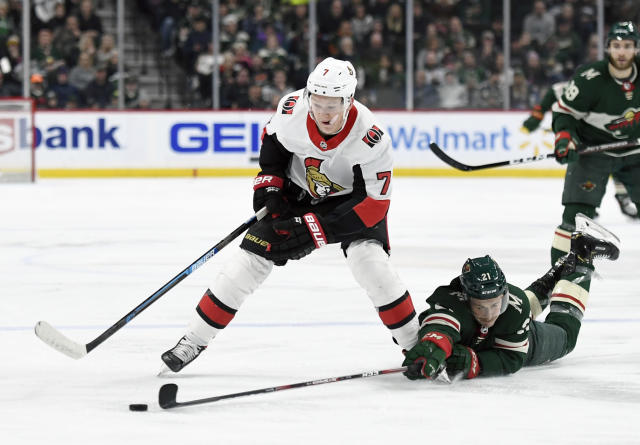 Minnesota Wild's Carson Soucy (21) attempts to get the puck from Ottawa Senators' Brady Tkachuk (7) during the second period of an NHL hockey game Friday, Nov. 29, 2019, in St. Paul, Minn. (AP Photo/Hannah Foslien)