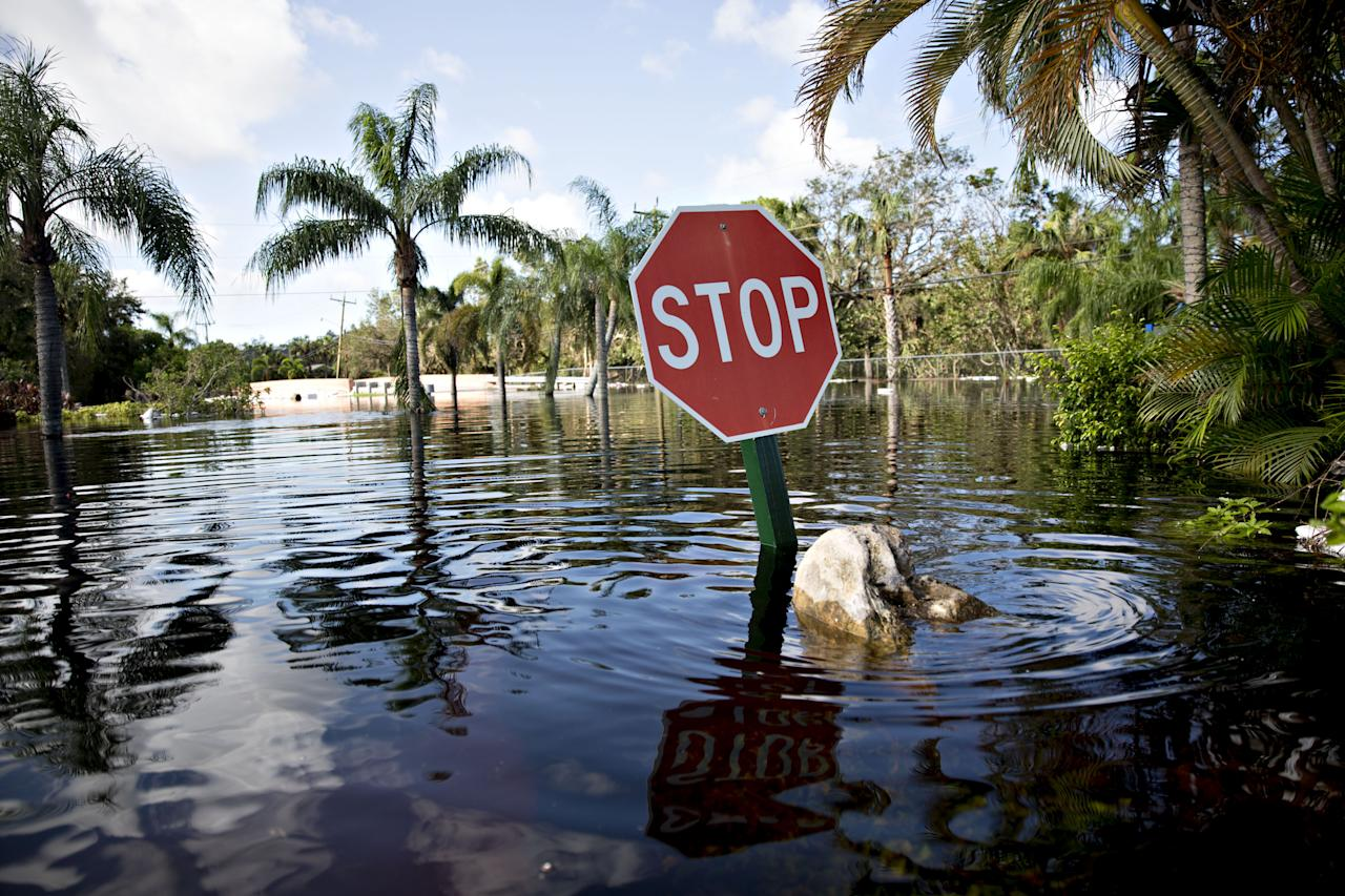 <p>A stop sign stands above flood waters in Bonita Springs, Fla, on Sept. 12, 2017. Hurricane Irma smashed into Southern Florida as a Category 4 storm, driving a wall of water and violent winds ashore and marking the first time since 1964 the U.S. was hit by back-to-back major hurricanes. (Photo: Daniel Acker/Bloomberg via Getty Images) </p>