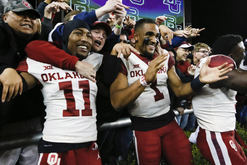 FILE - In this Nov. 16, 2019, file photo, Oklahoma cornerback Parnell Motley, left, and quarterback Jalen Hurts, right, celebrate with fans following an NCAA college football game against Baylor, in Waco, Texas. Motley and Hurts were selected to The Associated Press All-Big 12 Conference team, Friday, Dec. 13, 2019. (AP Photo/Ray Carlin, File)