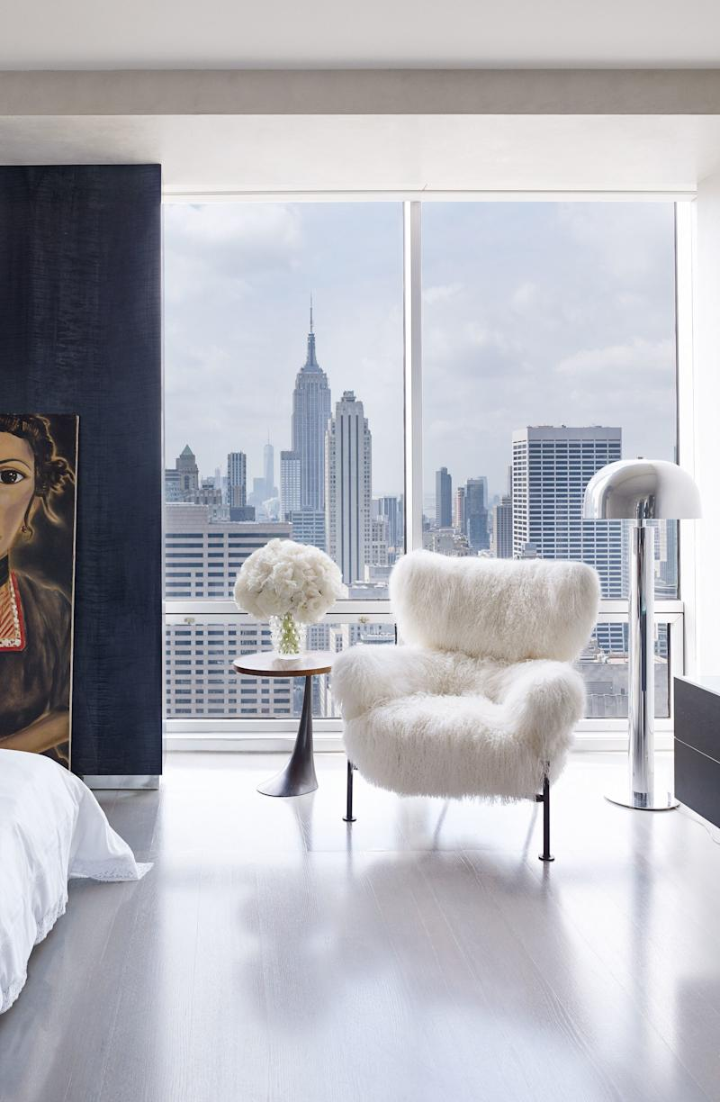 A view of the Empire State building from a one-bedroom apartment in Manhattan's Olympic Tower, with a Hervé Van der Straeten side table and a portrait by Francesco Clemente.