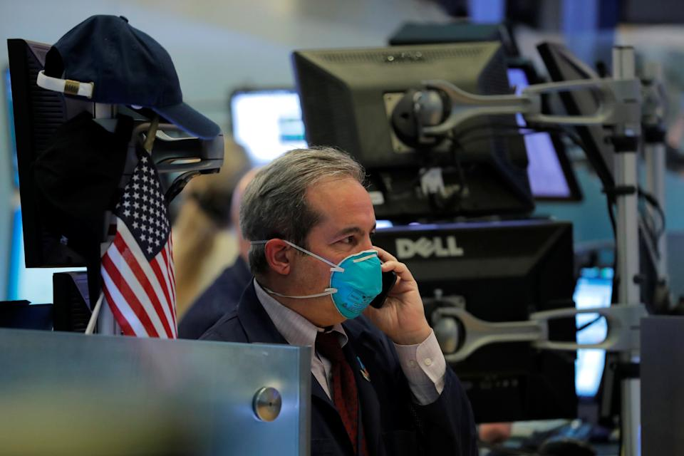 A trader wears a face mask on the floor of the New York Stock Exchange (NYSE) following traders testing positive for Coronavirus disease (COVID-19), in New York, U.S., March 19, 2020. REUTERS/Lucas Jackson     TPX IMAGES OF THE DAY