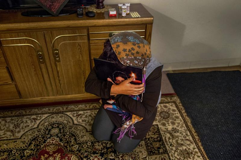 Shukriya Karimi, 36, drops to the floor, Thursday, Dec. 10, 2015, clenching a portrait of her son, one of two she had to leave behind in her war-torn country of Afghanistan. She has attempted suicide since arriving to the U.S. with her husband a Special Immigrant Visa holder. She was only allowed to bring her two younger children. (Photo: by Renée C. Byer/The Sacramento Bee)