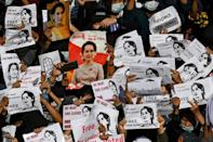 Protesters in Yangon hold signs with portraits demanding the release of detained Myanmar leader Aung San Suu Kyi