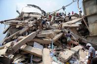 Bangladeshi volunteers and rescue workers are pictured at the scene after an eight-storey building collapsed in Savar, on the outskirts of Dhaka, on April 25, 2013