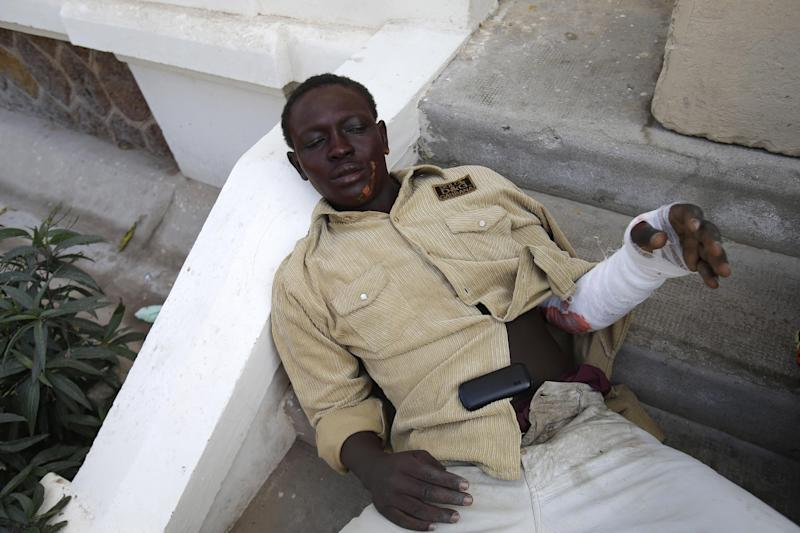 University student Mansour Niang, 27, who set himself on fire to protest grading changes that would keep him from continuing his studies, rests on steps outside the entrance to the emergency ward, after being treated for burns on his arm and face at the main municipal hospital, in Dakar, Senegal Friday, March 15, 2013. Niang and two other students who tried to immolate themselves Friday are part of a group of 50 geography majors who say a new grading system has unfairly left them one credit short of receiving their diplomas, and will block them from continuing to their fourth-year masters degree at the public university. Student witnesses said students unconnected to the protest immediately threw sand on Niang to put out the fire and stopped the two other students from setting themselves alight. (AP Photo/Rebecca Blackwell)
