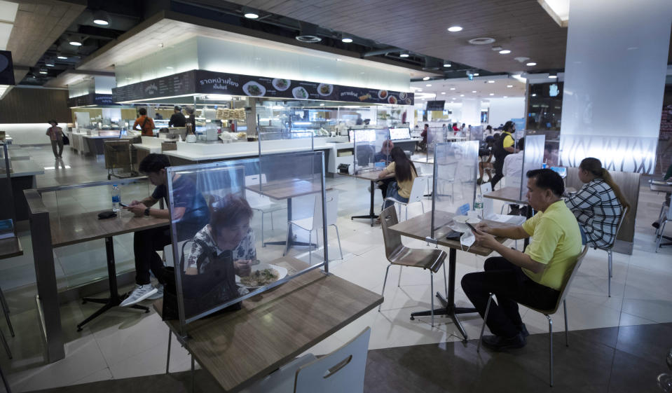 Peoples eat in a food court divided by plastic sheets designed to help reduce the spread of the coronavirus in Bangkok, Thailand, Monday, July 13, 2020. Daily life in the capital slowly returns to normal as Thai government has eased restrictions imposed weeks ago to combat the spread of COVID-19. (AP Photo/Sakchai Lalit)