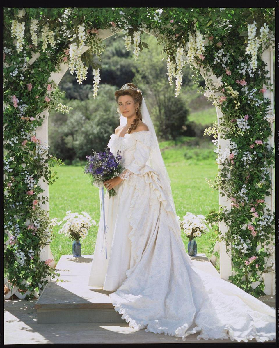 <p>Although a dress for the period drama <em>Dr. Quinn Medicine Woman, </em>Dr. Mike's wedding dress is still as dreamy as can be. For her wedding to Sully in Season 3, Dr. Mike wore an off the shoulder bustled taffeta gown with lace detailing throughout. The dress was made by her friends in Colorado Springs, who combined their own design for her with the dress her mother expected her to wear. </p>
