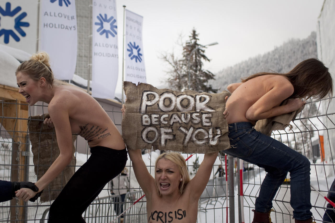 Topless Ukrainian protesters climb up a fence at the entrance to the congress center where the World Economic Forum takes place in Davos, Switzerland Saturday, Jan. 28, 2012. The activists are from the group Femen, which has have become popular in Ukraine for staging small, half-naked protests against a range of issues including oppression of political opposition. (AP Photo/Anja Niedringhaus)