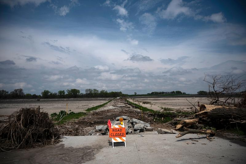 """A sign reading """"road closed"""" blocks a street destroyed by the flooding of the Elkhorn River near Scribner, Nebraska -- farmers in the area are suffering, their woes from a trade war with China compounded by the flood damage (AFP Photo/Johannes EISELE)"""