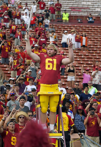 "Southern California long snapper <a class=""link rapid-noclick-resp"" href=""/ncaaf/players/263115/"" data-ylk=""slk:Jake Olson"">Jake Olson</a> leads the USC Trojan Marching Band following an NCAA college football game against Western Michigan, Saturday, Sept. 2, 2017, in Los Angeles. Olson lost his sight eight years ago to a rare form of retinal cancer, but joined the USC team on a scholarship for disabled athletes and began practicing with the Trojans 2 years ago. (AP Photo/Mark J. Terrill)"