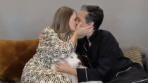 """In this video grab issued Sunday, Feb. 28, 2021, by NBC, Jodie Foster, left, holding her dog Ziggy, kisses her wife Alexandra Hedison as she accepts the award for best supporting actress in a motion picture for """"The Mauritanian"""" at the Golden Globe Awards. (NBC via AP)"""