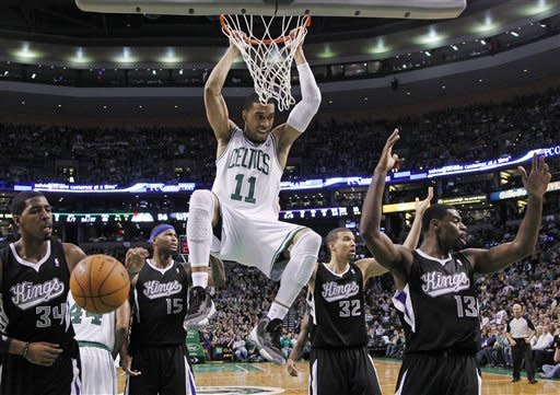 Boston Celtics guard Courtney Lee (11) hangs on after a dunk as Sacramento Kings forward Jason Thompson (34), center DeMarcus Cousins (15), guard Francisco Garcia (32) and guard Tyreke Evans (13) react during the first half of an NBA basketball game in Boston, Wednesday, Jan. 30, 2013. Offensive interference was ruled and the basket did not count. (AP Photo/Elise Amendola)