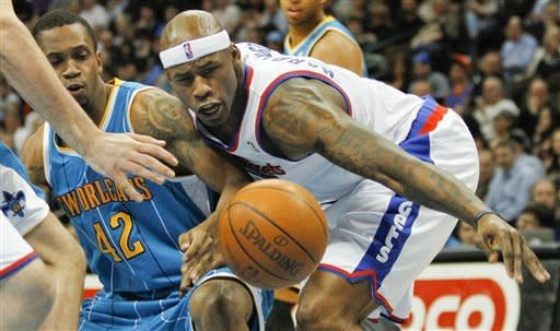 New Orleans Hornets forward Lance Thomas (42) and Denver Nuggets power forward Al Harrington (7) reach for a loose ball during the first quarter of an NBA basketball game Friday, March 9, 2012 in Denver. (AP Photo/Barry Gutierrez)