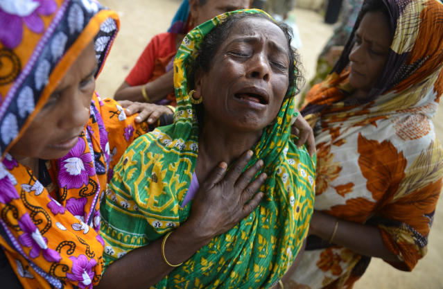 "A woman grieves as the body of a relative was brought to the morgue after it was pulled out from the rubble of a garment factory building that collapsed last week in Savar, near Dhaka, Bangladesh, Saturday, May 5, 2013. The death toll in the factory building collapse in Bangladesh rose to more than 530 on Saturday, a day after the country's finance minister downplayed the impact of the disaster on the garment industry, saying he didn't think it was ""really serious."" (AP Photo/Ismail Ferdous)"