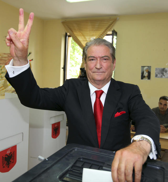 Prime Minister Sali Berisha of the Democratic Party gives a V sign and poses for photos before he casts his ballot during elections in Tirana, Albania, Sunday, June 23, 2013. Berisha and his close rival, Socialist leader Edi Rama, have hopes for eventual entry to the European Union, but the bloc has expressed concern over whether the country can manage to run fair and free elections. (AP Photo/Hektor Pustina)